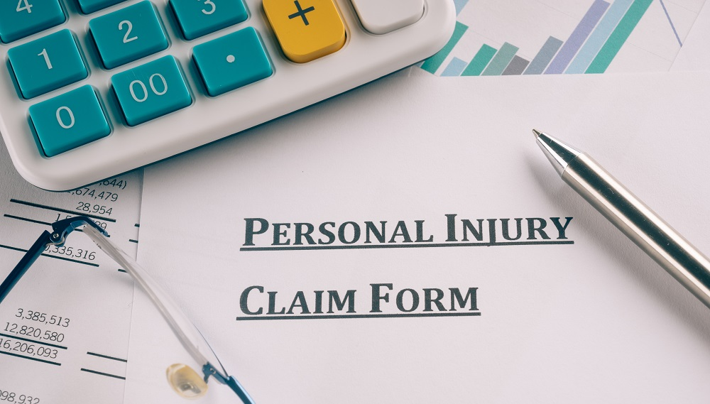 Partial part of calculator with teal buttons, partial view of reading glasses and silver pen on top of a paper form title PERSONAL INJURY CLAIM FORM, posing the question, What is personal injury in Hawaii?
