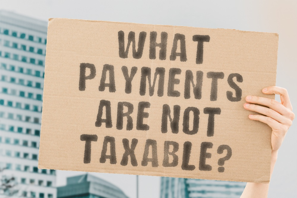 A cardboard sign being held up that says WHAT PAYMENTS ARE NOT TAXABLE?, referring to what kind of personal injury settlements are not taxable in Hawaii