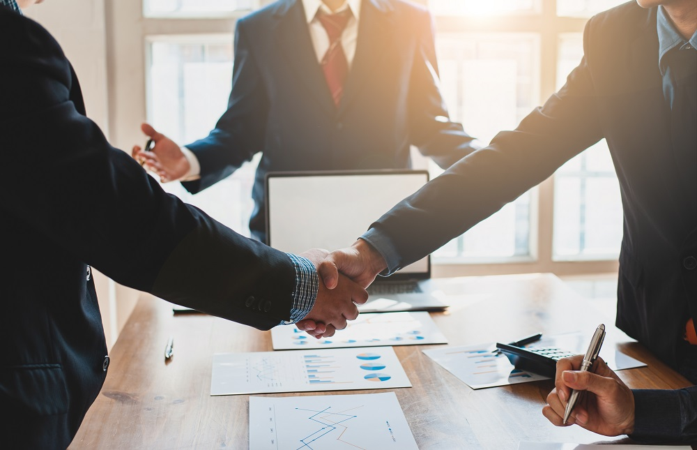 Two arms of men in suits sake hands over a conference table with a man in the suit from the neck down in the background, positing the question, Do Personal Injury Cases Settle After Deposition in Hawaii?