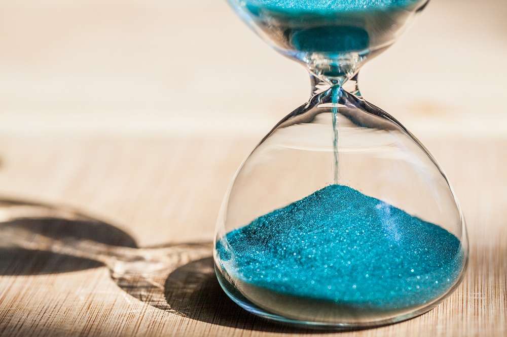 An hourglass with blue sand running from top to bottom sits on a sand colored towel in the sand, posing the question, How long does a personal injury lawsuit take in Hawaii?