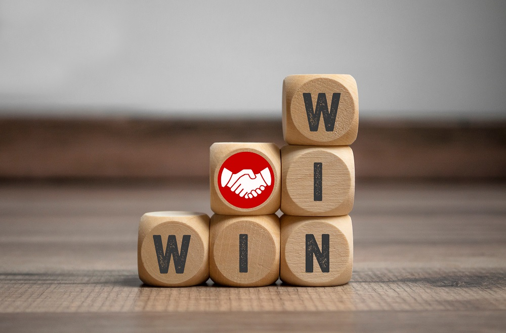Wooden blocks arranged to spell WIN right to left on the bottom, and from the top down on the right. A block woth white hands shaking on a red background is in the middle representing how to win a personal injury claim in Kona and Kamuela.